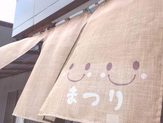 笑顔の暖簾(のれん)が風に揺れる